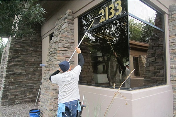 man cleaning exterior of commercial window